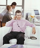 Man sitting on sofa in office, colleagues in background (focus on man)
