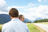 Boy (2-4 years) peering over father´s shoulder beside rural road