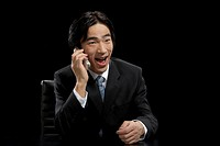 Businessman using mobile, laughing