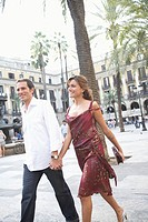 Spain, Barcelona, couple holding hands in Placa Real, smiling