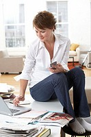 Woman sitting on table in lounge room, using laptop