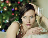 Woman sitting on sofa holding glass of champagne, portrait, close-up