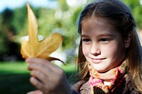 Girl (7-9) looking at leaf, close up