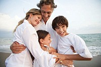 Family on beach, embracing, smiling, children (7-9)