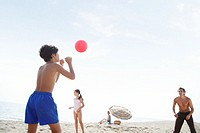 Father playing volleyball on beach with son and daughter (7-9)