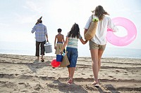 Family walking on beach carrying picnic box and toys, rear view