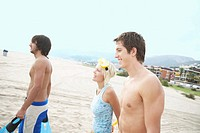Young woman and two young men walking on beach, man smiling