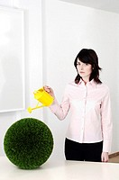 Businesswoman watering plants