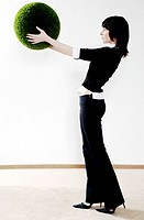 Businesswoman holding a grass ball