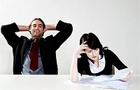 Businessman relaxing while his colleague is busy with her work
