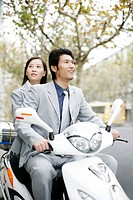 Businessman and businesswoman riding on a scooter.
