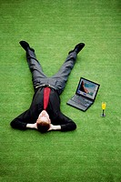Businessman resting on the field with his laptop by the side