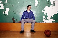 Businessman sitting in a basketball court