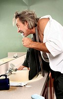 Businessman brushing teeth in the toilet