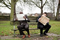 Two businessmen reading newspaper on the bench