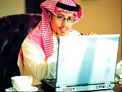 Saudi businessman working on laptop