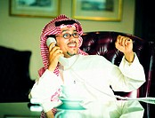Saudi businessman celebrating success while using a telephone