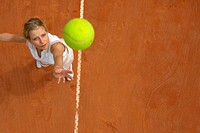 Top View of Female Tennis Player Mid-Serve (thumbnail)