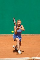 Front View of Female Tennis Player Hitting Ball