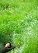 Young woman lying in field