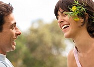 Young couple laughing, woman wearing flowers behind ear