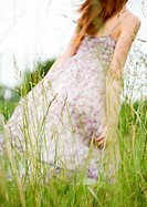 Young woman walking through grass, dress blowing in wind