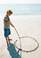 Boy drawing circle in sand
