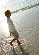 Boy walking in surf at beach