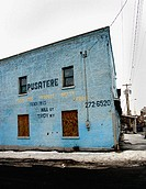 A blue, brick warehouse is captured in a city in the Northeastern United States during winter