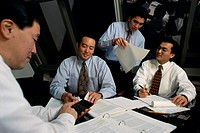 Four businessmen working in an office