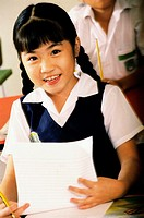 Portrait of a girl smiling holding a piece of paper