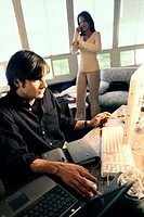 Young man working on a computer with a young woman standing behind him
