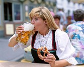 Drinking Beer and Eating Pretzel, Woman Dressed in Bavarian Costume, Mittenwald, Bavaria, Germany