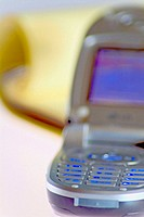 Close up of open cell phone with yellow notepad in background, selective focus