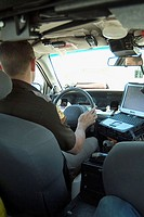 Rear view of a policeman driving a police car