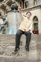 Asian man sits on the brim of a fountain and is laughing while pointing at something