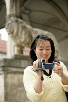 Young Asian woman with a camera standing in front of the ancient sculpture of a lion, selective focus