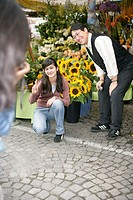 Person taking a picture of an Asian man and an Asian woman in front of a flower-booth (part of), focus on background