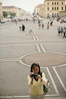 Asian woman standing on a plaze with a camera in her hand, selective focus