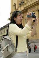 Young Asian woman with a camera standing in front of a Renaissance house, selective focus