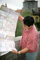 Asian man holding a map while standing on a bridge, selective focus