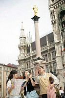 Asian family standing under the golden statue of the Virgin Mother, low angle view