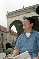 Asian man with a magazine in his hand in front of an antique building