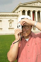 Asian man with a camera standing in front of an antique museum, close-up