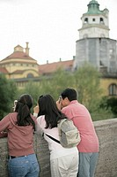 Three Asian people leaning on a bridge while taking pictures, selective focus
