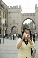 Young Asian woman with a camera standing in front of a big ancient gate, selective focus