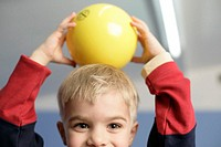 Boy holding ayellow ball over his head