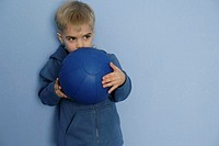Boy leaning against a wall, holding a blue ball