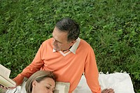 Mature couple sitting on grass, man reading a book