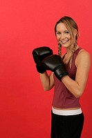 Young woman wearing sportswear and boxing gloves